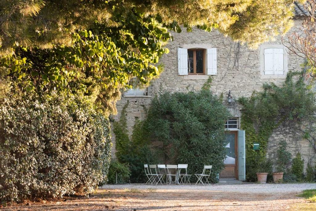 Photographie de la cour du Domaine d'Escarvaillac en Avignon, photographie prise au petit matin, on peut apercevoir l'entrée du caveau et une table de jardin