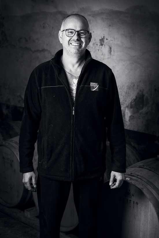 Portrait en noir et blanc de Michel Mathieu, responsable agricole du Domaine, la photographie a été prise dans la cave du domaine, des fûts de vieillissement en chêne sont au sol