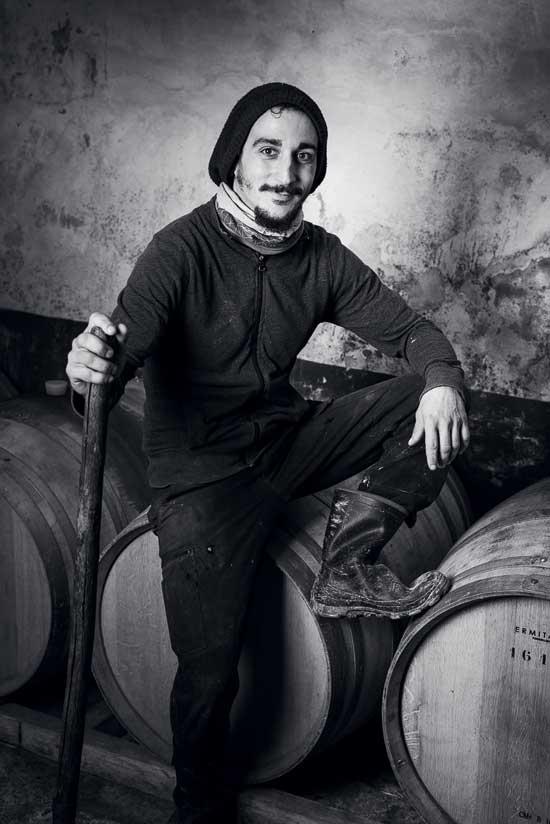 Portrait en noir et blanc de Sébastien Casaregola, aide agricole du Domaine, la photographie a été prise dans la cave du domaine, des fûts de vieillissement en chêne sont au sol