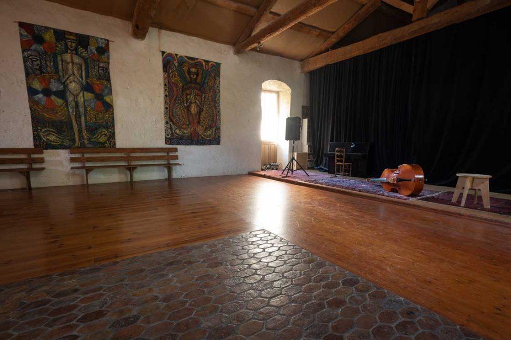 Photographie de la salle du grenier du Domaine Escarvaillac, il y a du parquet au sol ainsi qu'une scène où se déroule des concerts et des représentations théâtrales