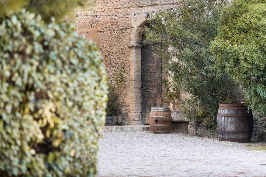 Photographie de la cour du Domaine d'Escarvaillac au petit matin, on peut apercevoir le portail et l'entrée de la salle voûtée