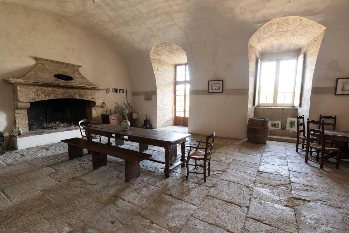 Photographie de la salle nommée la grande cuisine au Domaine d'Escarvaillac, il y a une grande cheminée, un table en chêne, le sol est dallé de vieilles pierres et de large fenêtre laisse rentrer la lumière du matin